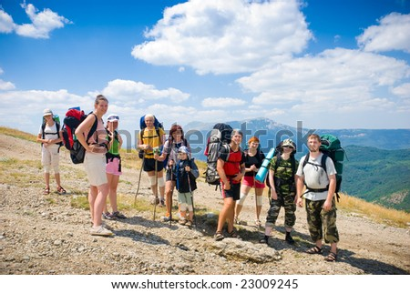 Hikers group on a slope in mountains - stock photo