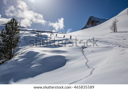 Hikers heading to top of mountain on snow-covered winter slopes in the Dolomites, Italian Alps
