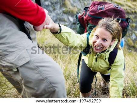 Hikers helping each other up a mountain. - stock photo