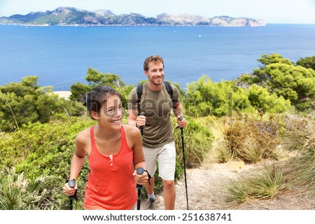 Hikers hiking in Mallorca, mediterranean Europe. Young adults couple walking in beautiful nature landscape on the coast of Mallorca, Balearic Islands, Spain. Famous European summer destination. - stock photo