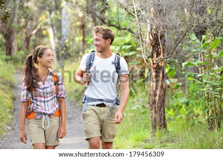Hikers - hiking people walking happy in forest. Hiker couple laughing and smiling. Interracial couple, Caucasian man and Asian woman on Big Island, Hawaii, USA. - stock photo