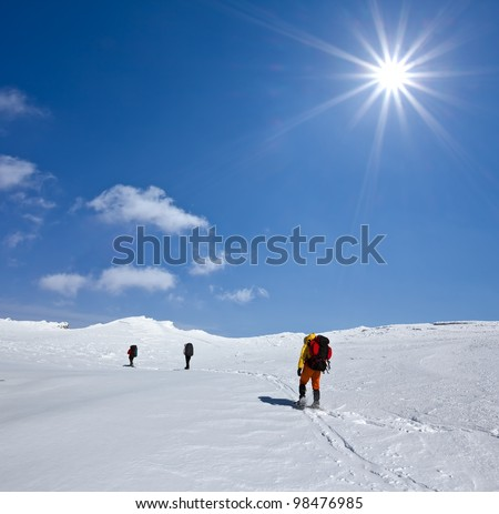 hikers in a snowbound plain - stock photo