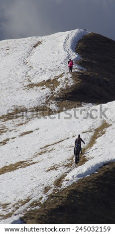 Hikers in a winter hillscape - stock photo