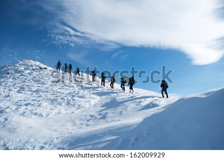 hikers in a winter mountain - stock photo