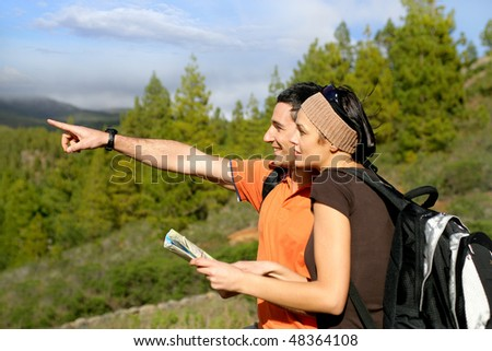 Hikers in countryside pointing at something - stock photo