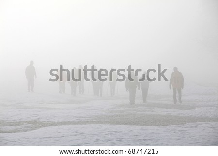 Hikers in fog - stock photo