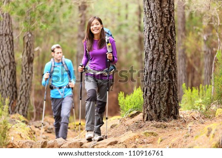 Hikers in forest. Couple hiking in fall forest. Asian woman hiker in front smiling happy. Photo from Aguamansa, Orotava, Tenerife, Canary Islands, Spain. - stock photo