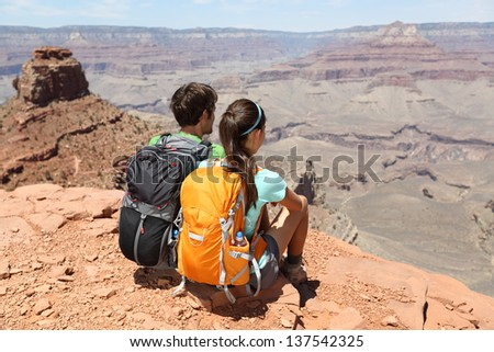 Hikers in Grand Canyon enjoying view of nature landscape. Young couple hiking relaxing during hike on South Kaibab Trail, south rim of Grand Canyon, Arizona, USA. - stock photo