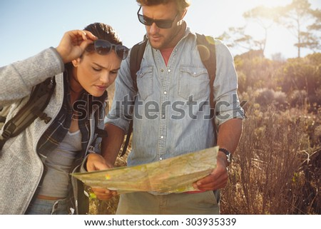 Hikers looking at map. Couple navigating together during travel hike outdoors in countryside. - stock photo