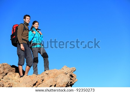 Hikers looking at view. Hiking young couple enjoying view looking at blue sky during hike. Multiracial couple with a lot of copy space. - stock photo