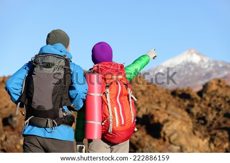 Hikers looking at view pointing hiking in mountain. People hiker couple in nature landscape trekking wearing backpacks. Woman and man on volcano Teide, Tenerife, Canary Islands, Spain - stock photo