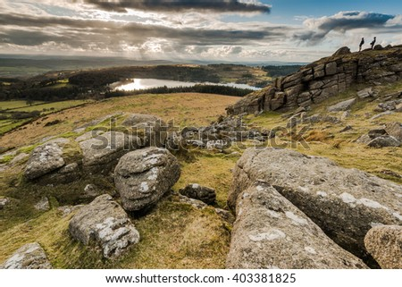 Hikers looking from hill top, adventure outdoors. Young people climbing rock formation in Dartmoor  National Park , dramatic sky and panoramic view over lake. - stock photo