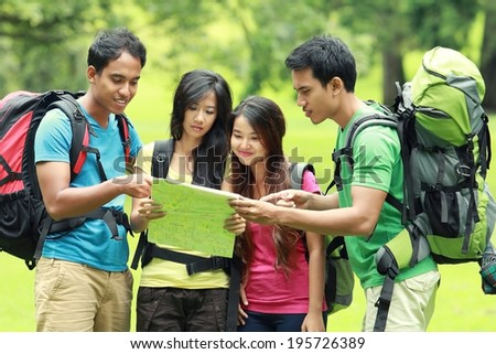 Hikers Looking The Map In Countryside together - stock photo