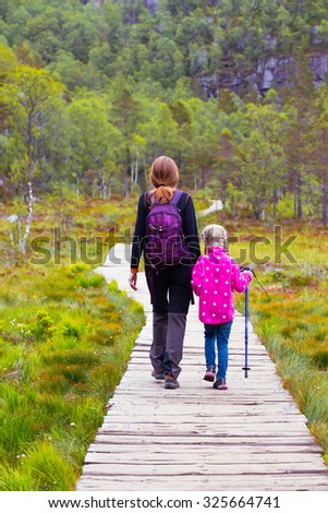 hikers mom and daughter walk along the trail through the woods on  Preikestolen, norway - stock photo