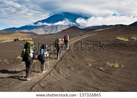 Hikers moving on volcano land in Kamchatka, Russia. - stock photo
