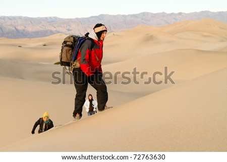 Hikers on a Desert Sand Dune in Winter - stock photo