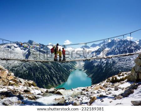 Hikers on a suspension bridge - stock photo