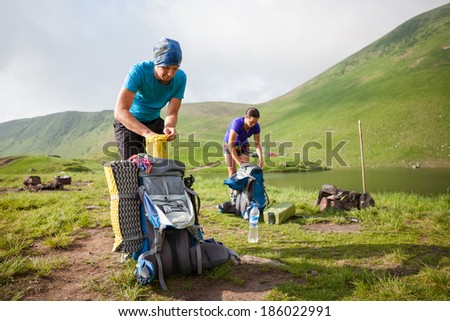 Hikers pack their backpack at camp - stock photo