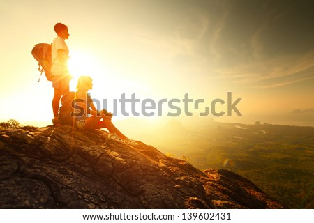Hikers relaxing on top of a mountain and enjoying sunrise - stock photo
