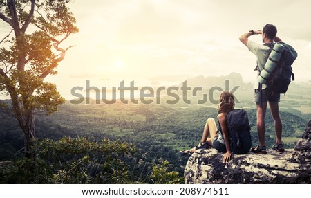 Hikers relaxing on top of the mountain and enjoying green valley view - stock photo