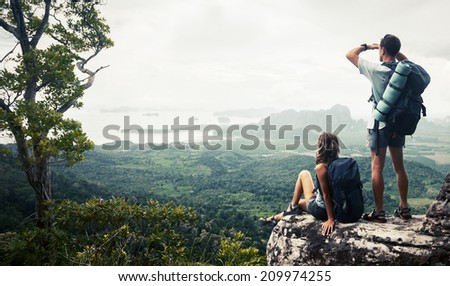 Hikers relaxing on top of the mountain and enjoying valley view - stock photo