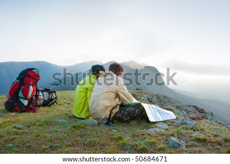 Hikers sit on the peak and exploring the map - stock photo
