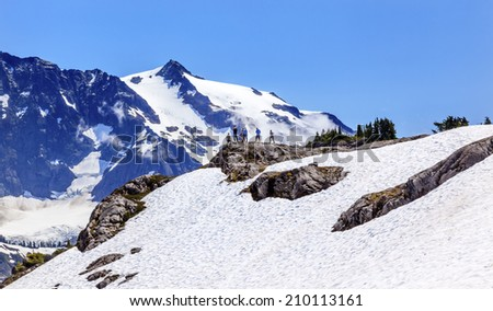 Hikers Snowfields Glaciers Artist Point Mount Shuksan Mount Baker Highway Snow Mountain Washington State Pacific Northwest - stock photo