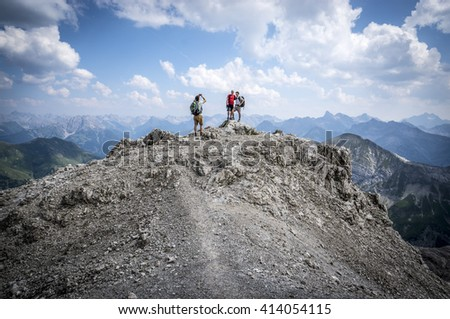 Hikers take pictures on a rocky mountain of the Allgau Alps - stock photo
