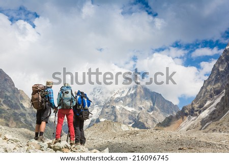 Hikers team and snow-capped mountain landscape - stock photo