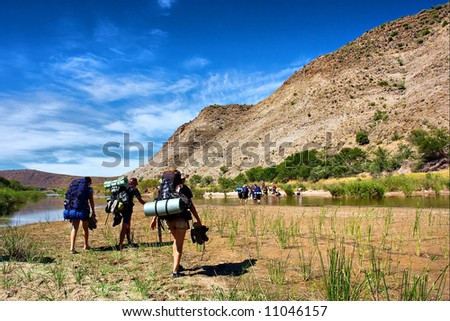 Hikers walk across awesome river in mountains. Shot in the Langeberge highlands near Grootrivier, Garden Route, Western Cape, South Africa. - stock photo