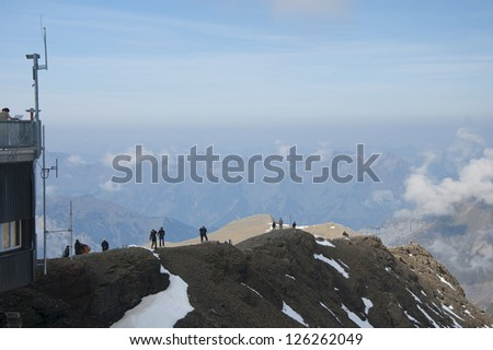 Hikers walk down mountain ridge with mountains in distance - stock photo