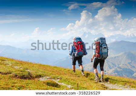 hikers walking in mountains - stock photo