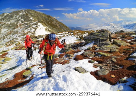 Hikers walking on snow covered path on top of the mountains - stock photo