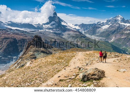 Hikers walking on spectacular mountain scenery, Matterhorn in background, Alps, Switzerland.