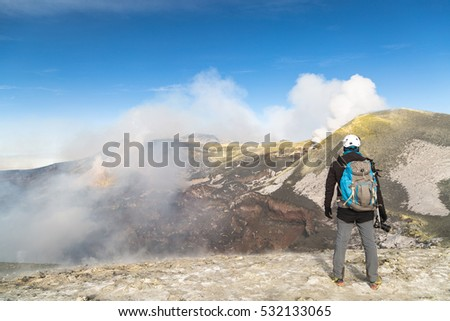 Hikers watch the inside of the central crater of Mount Etna