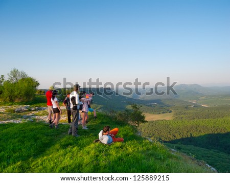 Hikers watch the terrain from the peak of a cliff