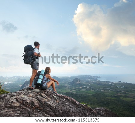 Hikers with backpacks enjoying valley view from top of a mountain - stock photo