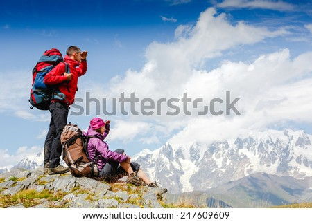 Hikers with backpacks standing on top of a mountain and enjoying the view  - stock photo