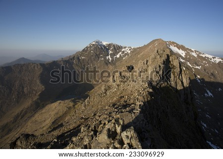 hiking across rocky mountain ridge in north wales on a sunny day - stock photo