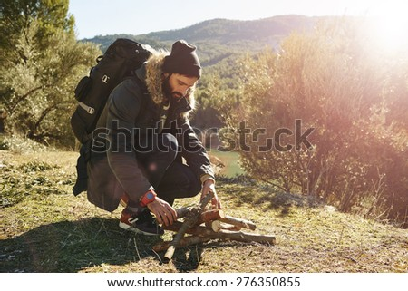 Hiking. Adventure hiking man trying to light a fire during a trip in mountains to keep warm after a long hike. Healthy lifestyle photo of Caucasian breaded man.    - stock photo