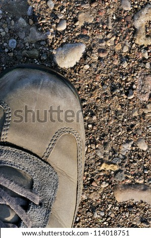 Hiking boot off-road shoe on hard arid dried soil, rough terrain vertical close up, detailed macro of bare earth, dust, stones, rocks, pebbles, sand, ash - stock photo