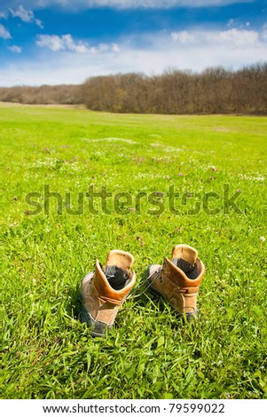 Hiking boot on the meadow - stock photo