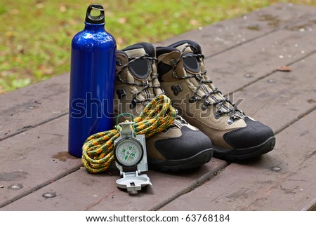 Hiking boots, canteen and compass in the table. Shallow depth of field and blurred background - stock photo