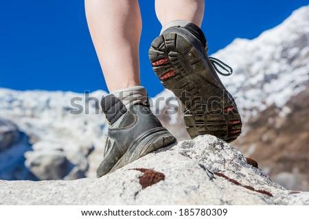 Hiking boots closeup on mountain rocks in Himalayas  - stock photo