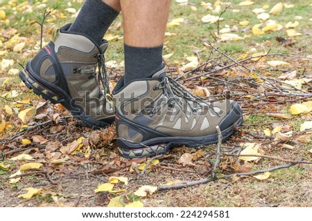 Hiking boots in autumn scenery - stock photo