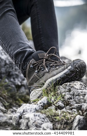 Hiking boots. Mountain landscape. Dirty earth and stones
