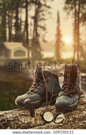 Hiking boots with compass on tree trunk at campsite - stock photo
