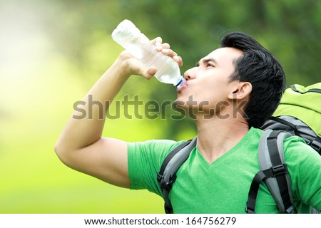 hiking concept. thirsty man having a break drinking a bottle of water - stock photo