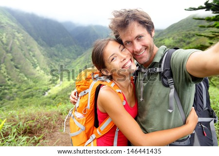 Hiking couple - Active young couple in love. Couple taking self-portrait picture on hike. Man and woman hiker trekking on Waihee ridge trail, Maui, USA. Happy romantic interracial couple. - stock photo