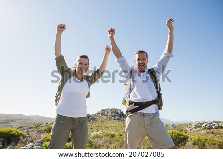 Hiking couple cheering at camera on mountain terrain on a sunny day